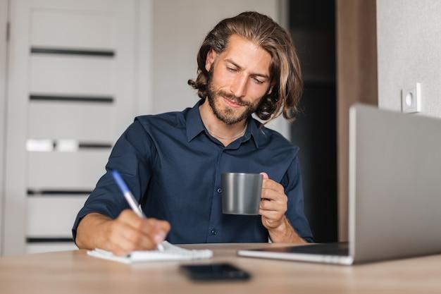 긴 머리를 가진 잘생긴 남자는 집에 있는 탁자에 앉아 있는 공책에 글을 씁니다.