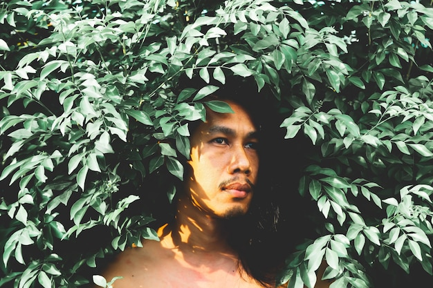 Handsome man with long hairstyle posing with plant. vintage and film filter style