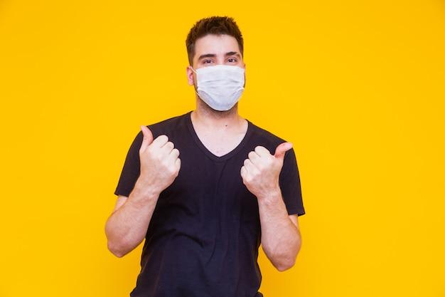彼の顔にマスカラcirurgicaを持つハンサムな男。コロナウイルスの概念