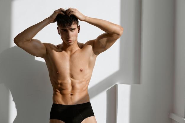 黒いパンティーのトリミングされたビューで筋肉質の裸の体を持つハンサムな男