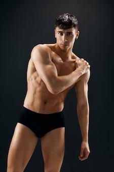 Handsome man with naked muscular body in dark panties bodybuilder