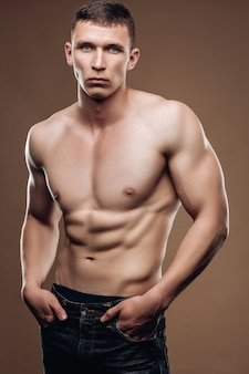 裸の胴体、筋肉質の腕、キューブを押すハンサムな男はジーンズに、ポケットに手を入れています。スタジオ写真。