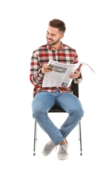 Handsome man with newspaper sitting on chair against white