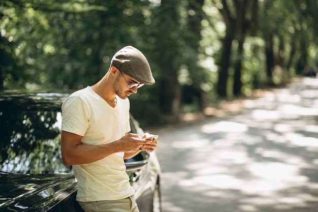 Handsome man with phone by car