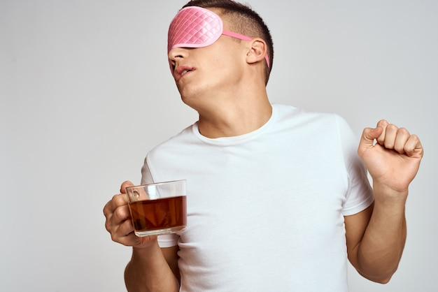 Handsome man with pink sleep mask and with a cup of tea in hand