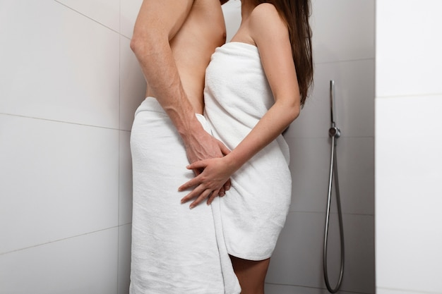 シャワーの中に立って抱き締めるきれいな女性とハンサムな男。若いカップルの愛とキス。