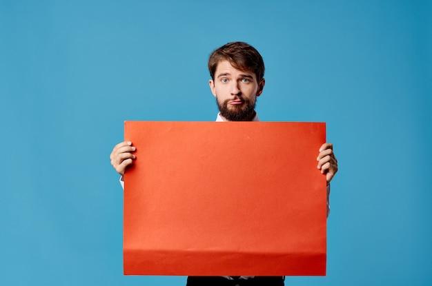 赤いモックアップポスターサインコピースペースクローズアップを持つハンサムな男 Premium写真