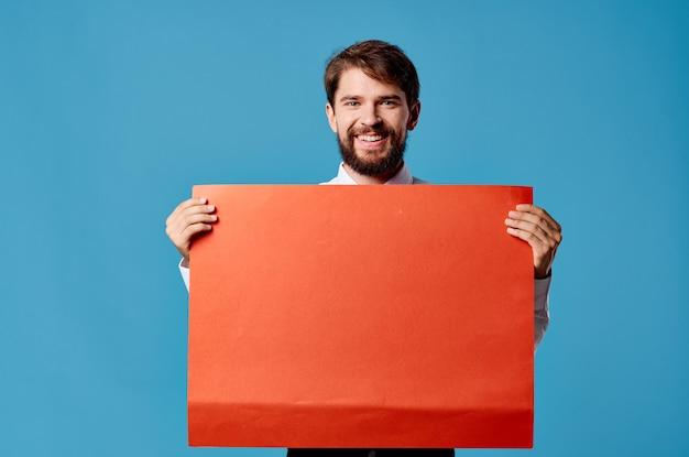 Красивый мужчина с красным макетом плаката подписывает крупный план copyspace