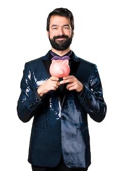 Красивый мужчина с блестками куртки держит piggybank