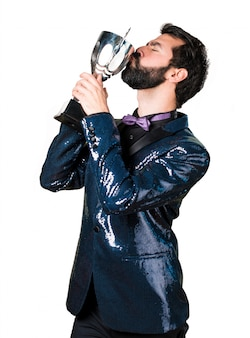Handsome man with sequin jacket holding a trophy