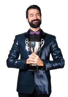 Uomo bello con giacca di sequin che tiene un trofeo