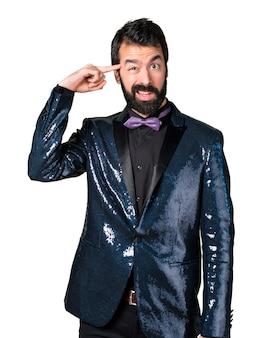 狂ったジェスチャーを作るスパンコールジャケットを持つハンサムな男