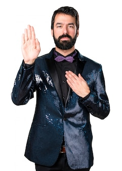Handsome man with sequin jacket making an oath
