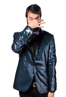 Handsome man with sequin jacket making smelling bad gesture