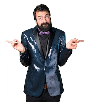 Handsome man with sequin jacket pointing to the laterals having doubts