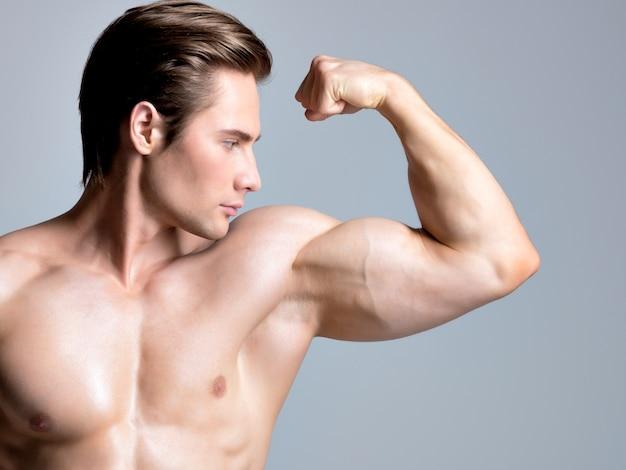 セクシーな筋肉の美しい体のポーズを持つハンサムな男