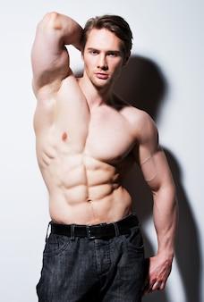 Bell'uomo con sexy muscoloso bel corpo in posa