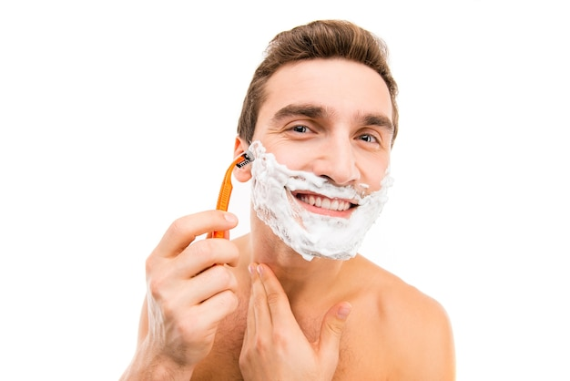 Красивый мужчина с пеной для бритья на лице и бритвой