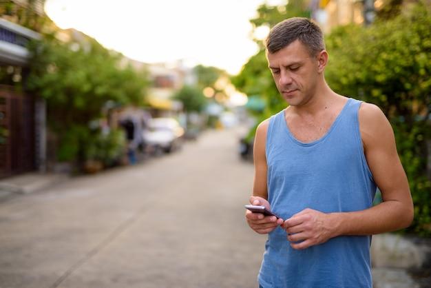 屋外の通りでリラックスした短い髪のハンサムな男