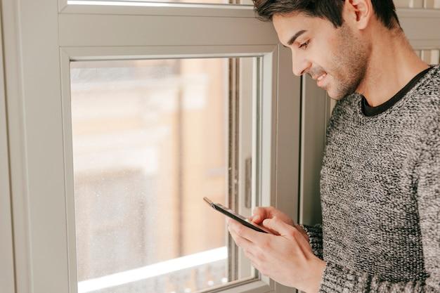 Handsome man with smartphone near window