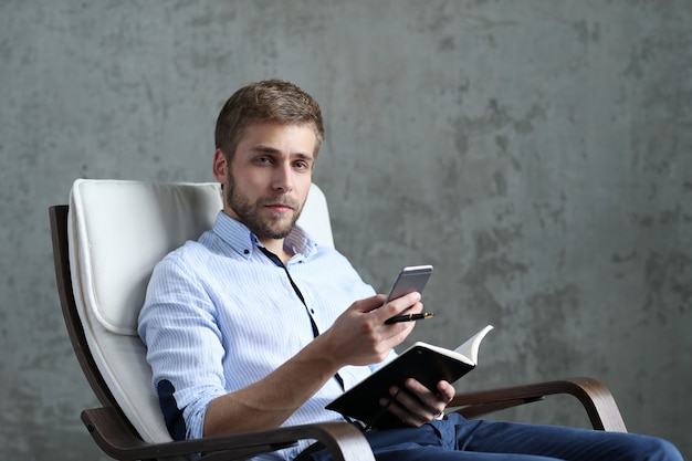 Handsome man with smartphone and notebook
