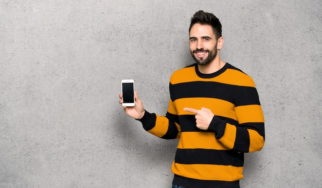 Handsome man with striped sweater happy and pointing the mobile over textured wall