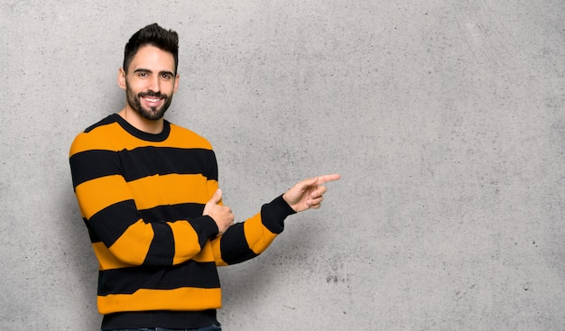 Handsome man with striped sweater pointing finger to the side in lateral position over textured wall