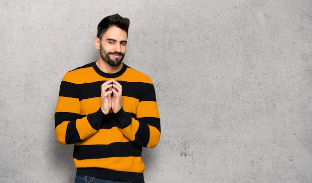 Handsome man with striped sweater scheming something over textured wall