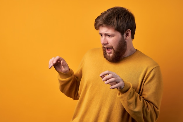 세련된 머리카락과 수염을 가진 잘 생긴 남자가 데이트에 그의 여자 친구와 함께 공포 영화를보고 겁 먹은 표정으로 비명