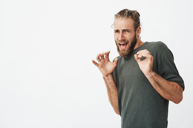Handsome man with stylish hair and beard screaming with frightened expression