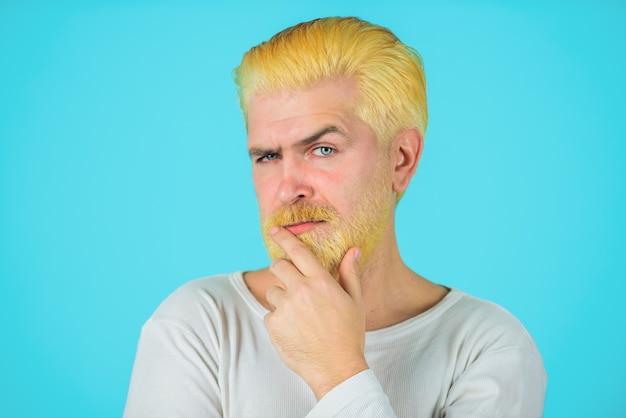 スタイリッシュなヘアカット理髪店のコンセプトを持つハンサムな男漂白された髪とひげを持つ現代人