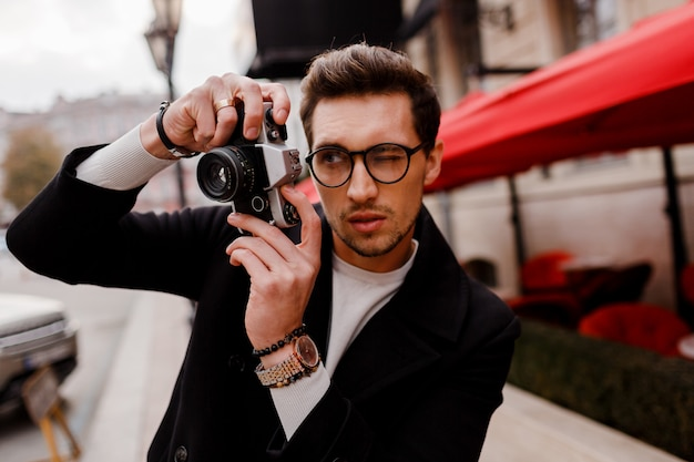 Handsome man with stylish hairstyle making photod in european city. autumn season.