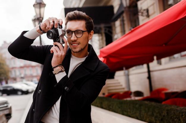 Красивый мужчина со стильной прической, делая фото в европейском городе. осенний сезон.