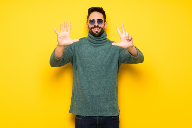 Handsome man with sunglasses counting eight with fingers