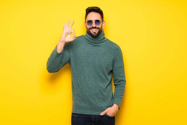 Handsome man with sunglasses showing an ok sign with fingers
