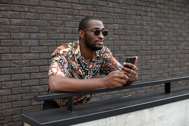 Handsome man with sunglasses using modern smartphone outdoors