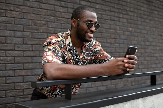 야외에서 현대적인 스마트폰을 사용하여 선글라스를 낀 잘생긴 남자
