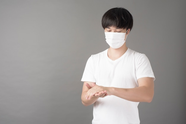Handsome man with surgical mask is using alcohol hand sanitizer