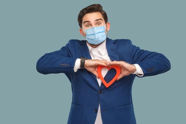 立って赤いハートの形を保持し、カメラを見て青いジャケットのサージカルマスクを持つハンサムな男。医学とヘルスケアの概念。屋内、青い背景で隔離のスタジオショット
