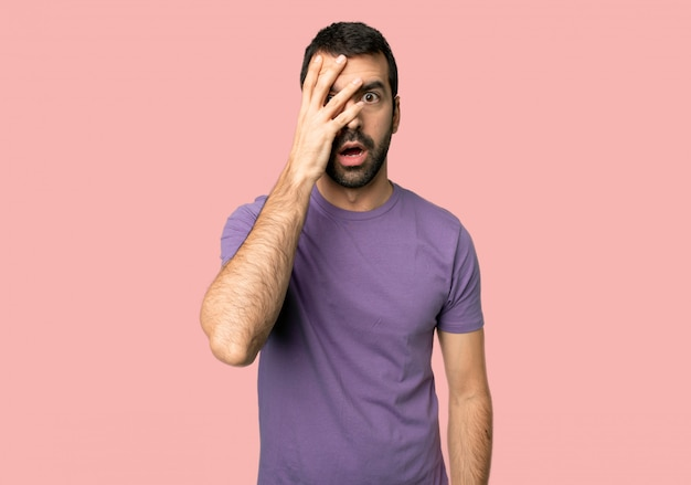 Handsome man with surprise and shocked facial expression on isolated pink background