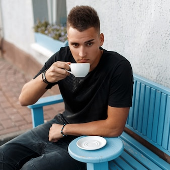 Красивый мужчина с прической в черной рубашке сидит на синей скамейке и пьет кофе.