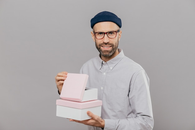 Handsome man with thick stubble, pleasant smile, holds boxes in hands, opens gift with happiness