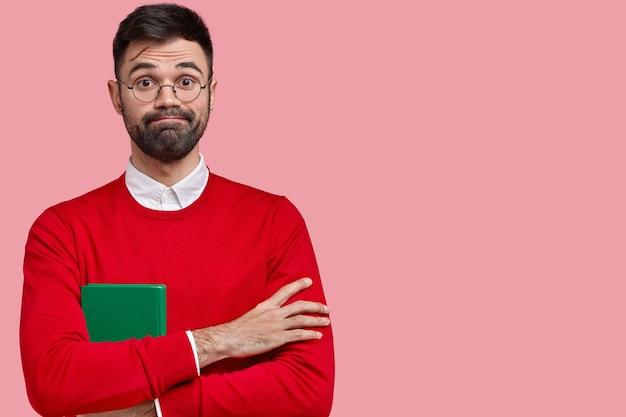 Красивый мужчина с густой щетиной, сжимает губы, скрещивает руки, несет зеленую тетрадь для записей, носит красный джемпер