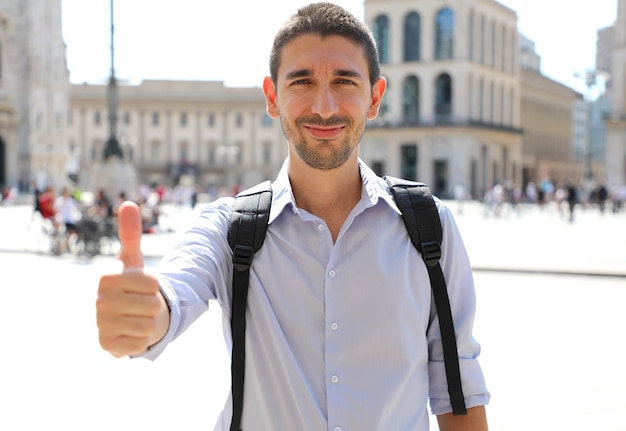 Handsome man with thumbs up in city street