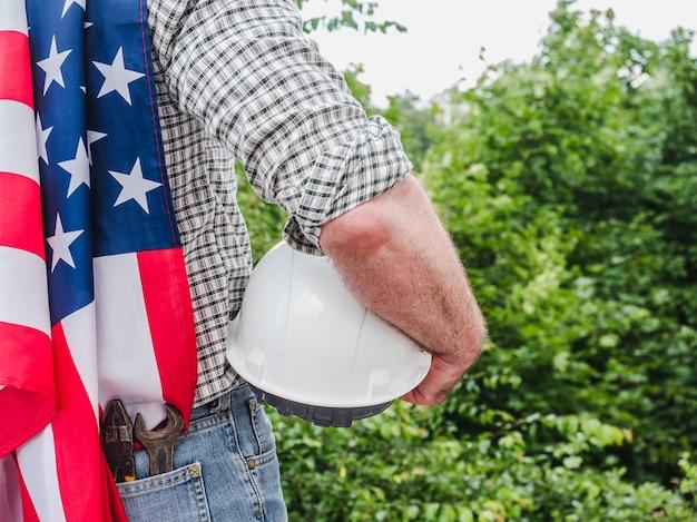 アメリカの国旗を保持しているツールを持つハンサムな男