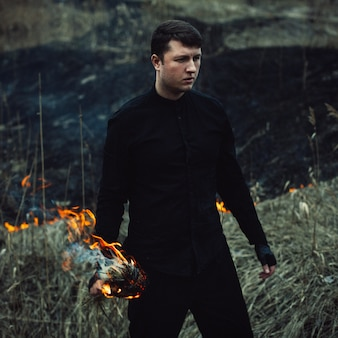 Handsome man with a torch in his hands sets fire to the grass in the field