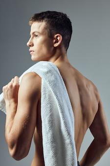 Красивый мужчина с полотенцем на плечах обнаженный торс изолированный фон