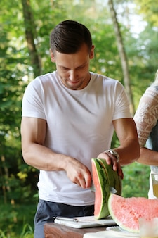 Handsome man with white t-shirt cutting watermelon