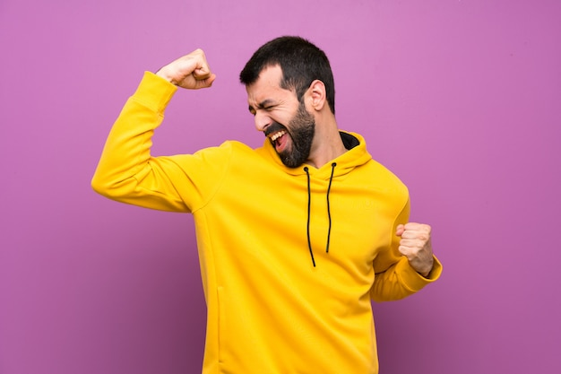 Handsome man with yellow sweatshirt celebrating a victory