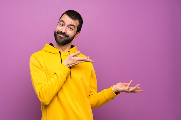 Handsome man with yellow sweatshirt extending hands to the side for inviting to come